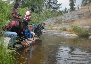 """During the Confederated Colville Tribe's First Salmon Ceremony's sunrise service, participants are encouraged to click river rocks together streamside, to """"call the salmon home."""""""